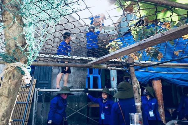 Các bạn sinh viên tình nguyện ĐH Vinh giúp bà con nhân dân Kỳ Phú chỉnh trang nhà ở dân cư.